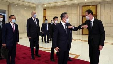 الرئيس بشار الأسد ووزير الخارجية الصيني. (أ ف ب)