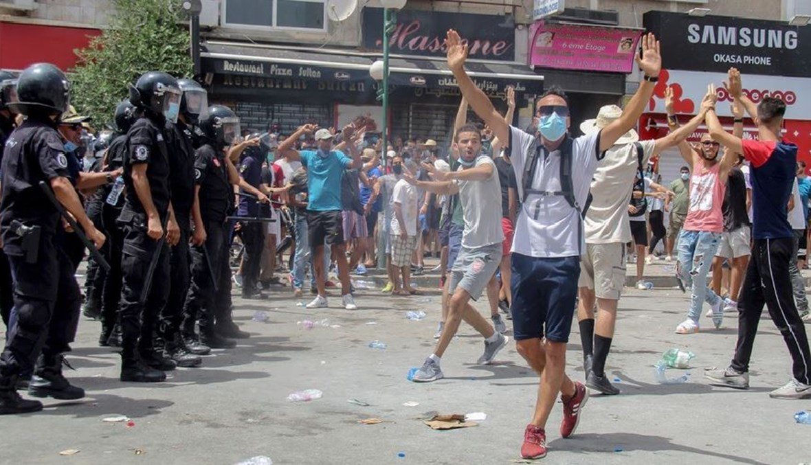 محتجون يقفون مقابل الأمن خلال تظاهرات تونس أمس (ا ب)