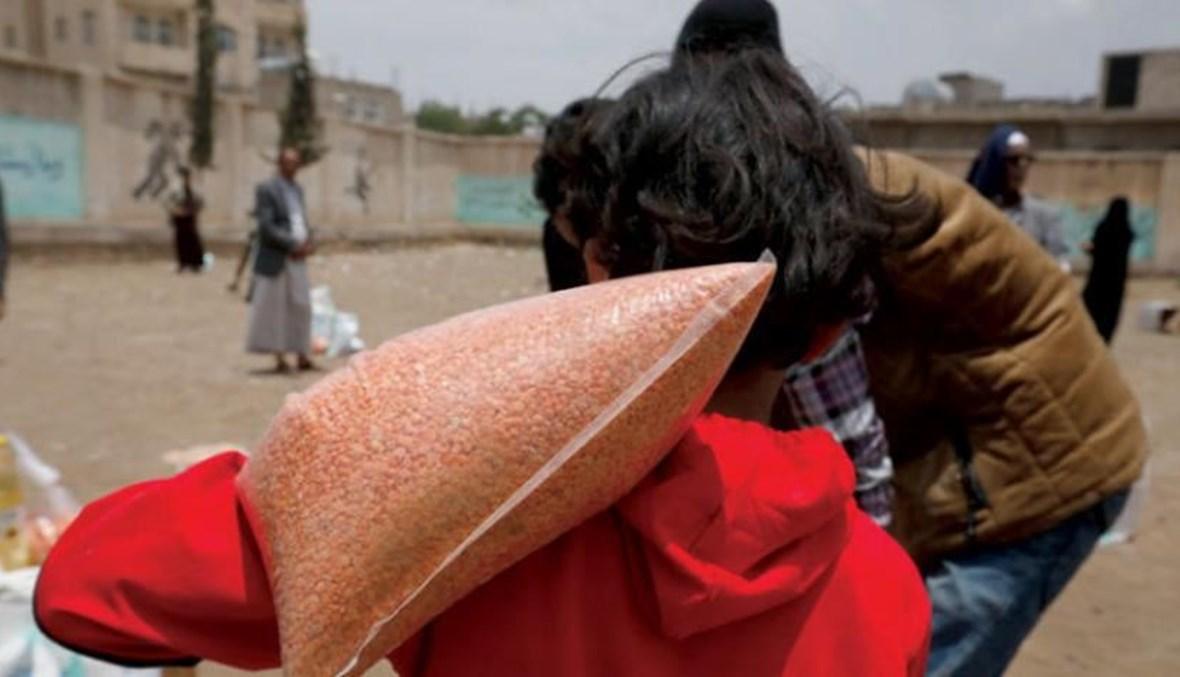طفل يحمل مساعدات غذائية بمخيم نازحين في صنعاء