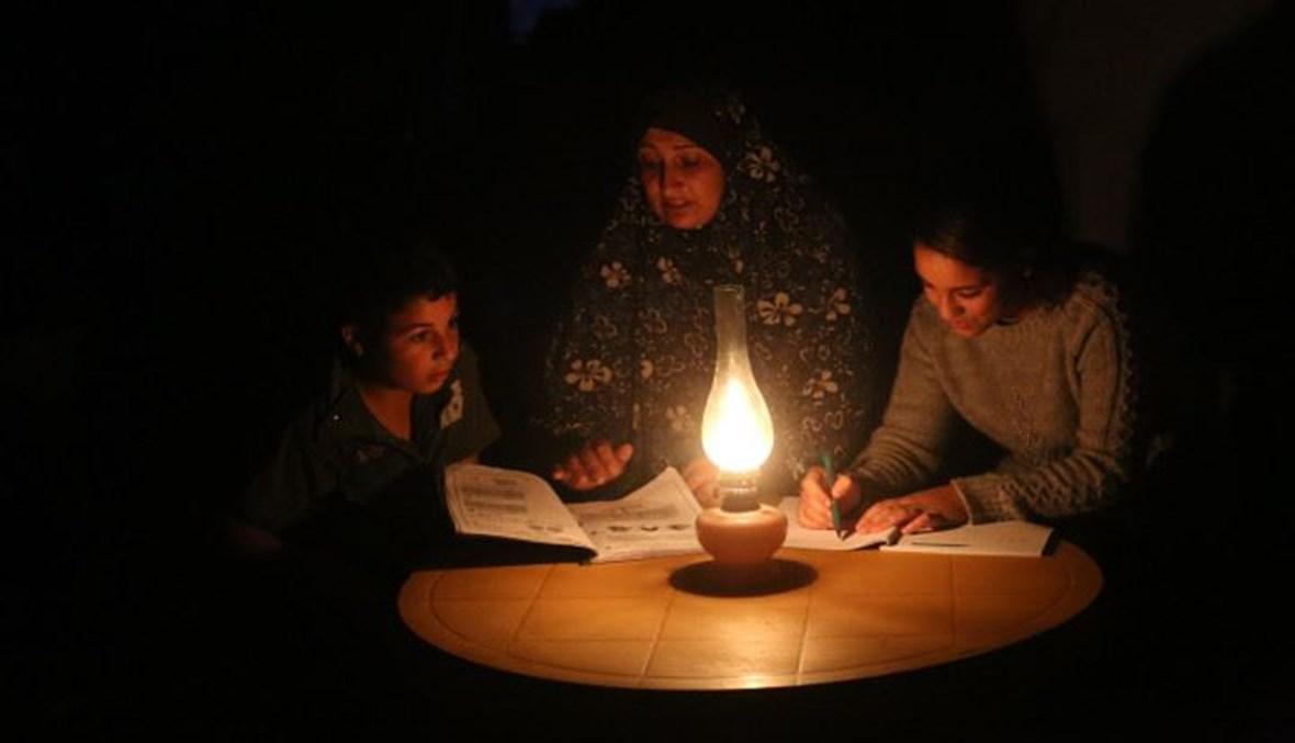 سيدة تتابع دراسة اطفالها على ضوء الشمعة في غزة