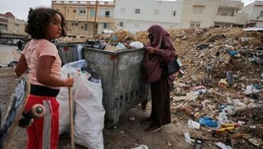 جميلة غويلي (55 عاما) أم تونسية تنبش في أكوام القمامة الملقاة بحثا عن زجاجات بلاستيكية فارغة لبيعها لشراء الطعام لأسرتها في العاصة التونسية تونس في 31 تموز 2021
