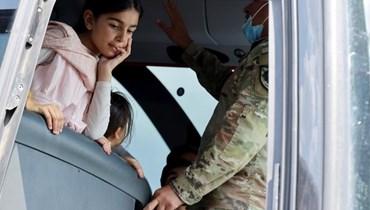 فتاة تستمع إلى مترجم عسكري أثناء وصولها مع أشخاص آخرين إلى فيرجينيا