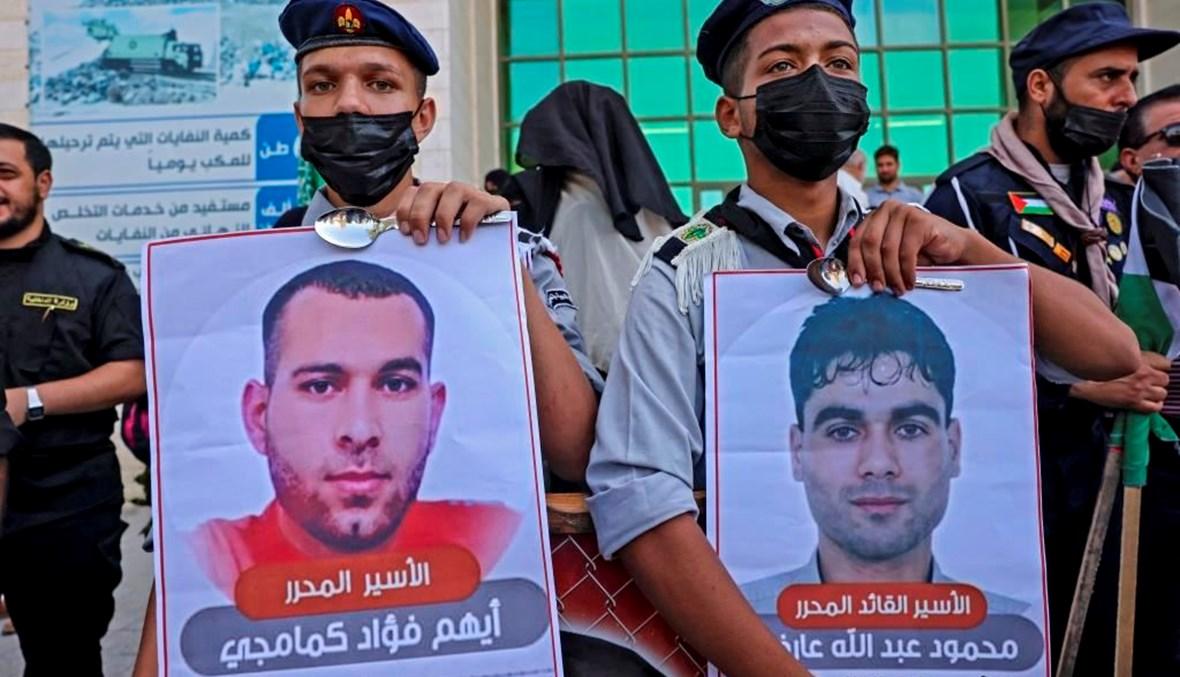 شبان فلسطينيون يحملون صورتين لاثنين من الأسرى الستة الفارين (ا ف ب)