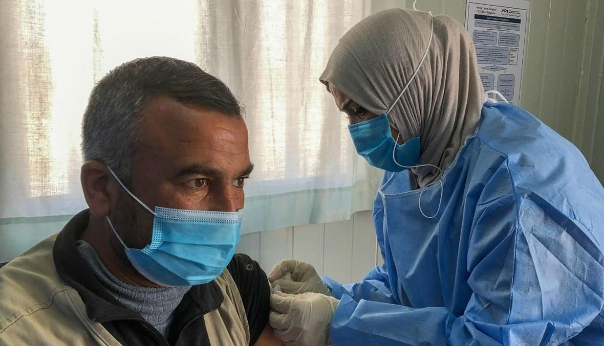 لاجئ سوري يتلقى اللقاح في مخيم الزرقا في الأردن