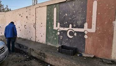 متطوع ليبي خلال أعمال إعادة ترميم مدرسة تضررت جرّاء القتال في إحدى ضواحي طرابلس