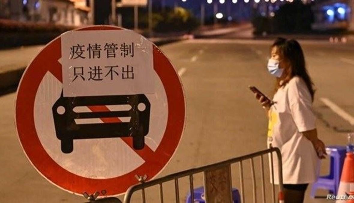 سيدة تقف عند تقاطع شارع خال من الحركة في الصين