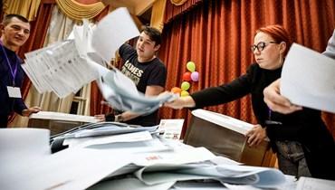 أعضاء لجنة انتخابية محلية يفرغون صندوق اقتراع بعد اليوم الأخير من الانتخابات البرلمانية في موسكو (ا ف ب)