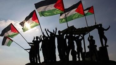 فلسطينيون يرفعون علم بلادهم