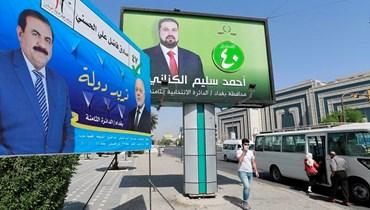 عراقي يمر أمام لافتة انتخابية تظهر مرشحين للانتخابات النيابية في بغداد (أ ف ب)
