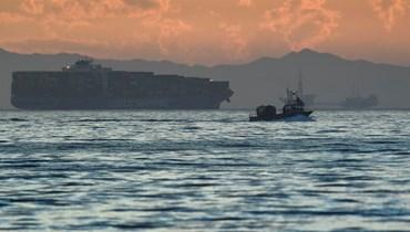 قارب يبحر عبر منصة نفطية وسفينة حاويات شحن في كاليفورنيا (أ ف ب)