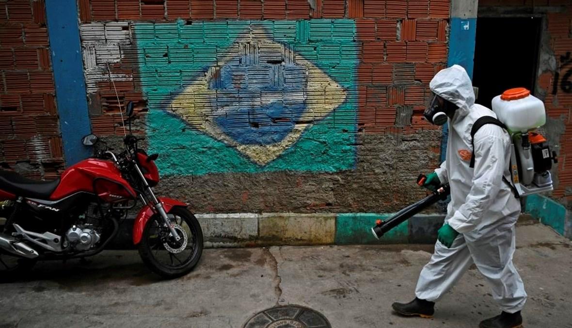 متطوع يرتدي معدات الوقاية الشخصية يمر أمام لوحة جدارية تصور العلم البرازيلي أثناء تطهير منطقة في ريو دي جانيرو (أ ف ب)